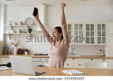 Excited latina woman freelancer raise hands up hold phone scream hooray in delight celebrate finish work on difficult project. Euphoric young lady remote employee meet deadline with all the work done Foto stock ©