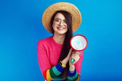 Excited lgbt activist leader girl in rainbow sweater speaking in megaphone and smiling while standing against blue background.