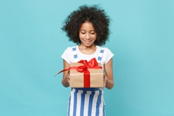 Excited little african american kid girl 12-13 years old in striped clothes isolated on blue background. International Women's Day birthday, holiday concept. Hold red present box with gift ribbon bow