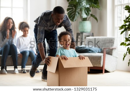 Excited little black boy sit in cardboard box playing with young dad unpacking packages on moving day, happy young African American family have fun entertain with small kids relocating to new home