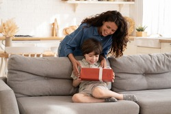 Excited little boy receiving birthday present from mum sitting on sofa in living room. Children holiday celebration concept with loving mother giving gift to adorable preschool son congratulating kid