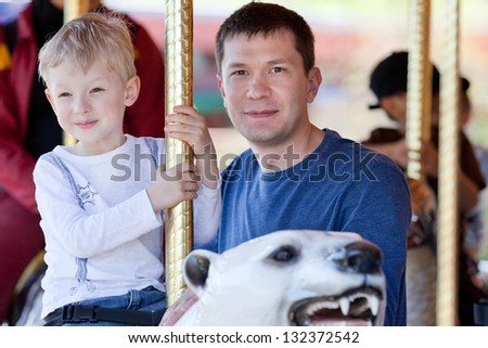 excited little boy riding a merry-go-round at the amusement park with his father