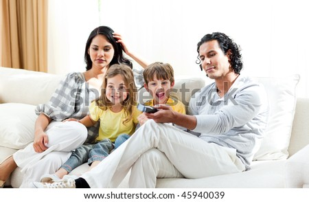 Excited little boy watching TV with his family sitting on a sofa