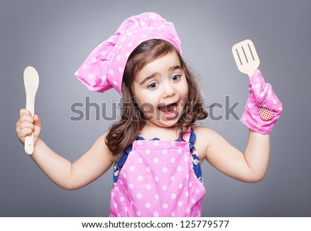 excited little cook posing with open moth and spoons in her hands