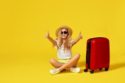 excited little girl with suitcase and passport sitting on floor