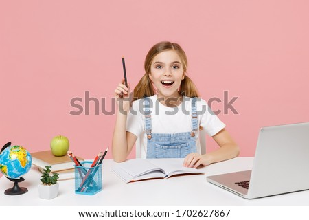Excited little kid schoolgirl 12-13 years old study at desk with pc laptop isolated on pink background. School distance education at home during quarantine concept. Point pen up with great new idea