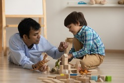 Excited little son and loving dad of indian ethnicity have fun play toys on warm floor at living room. Young male babysitter and preschooler boy engaged in education game with wooden blocks dinosaurs