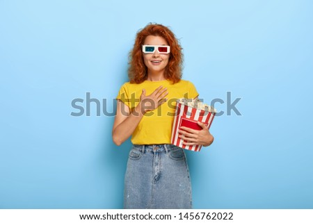 Excited lovely cheerful female has wavy red hair, touches chest reacts on touching scene in film, wears 3d glasses, being glad and impressed eats popcorn from bucket. Time for watching movie at cinema