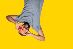 Excited mad man spectator hanging upside down and looking through binoculars from grapefruit over isolated yellow studio background. watching, observation, expression. Copy space for text.