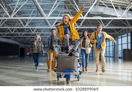 Excited male and female people running to departure gate. One of them is wheeling baggage cart with woman sitting on the top