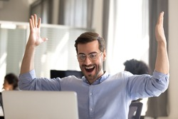 Excited male employee look at screen scream with happiness witness sales rising or project success, happy man worker gesture yes winning lottery online, hit jackpot triumph in web game