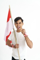 excited male holding indonesian flag. patriotic nationalism concept of indonesia independence day