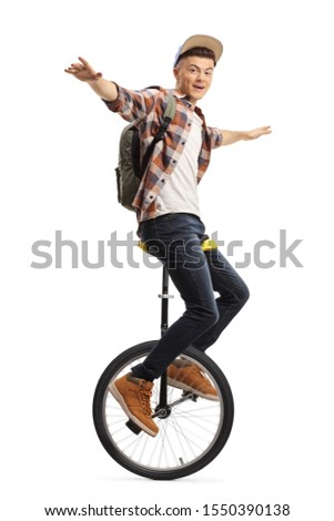 Excited male student riding a unicycle isolated on white background #1550390138