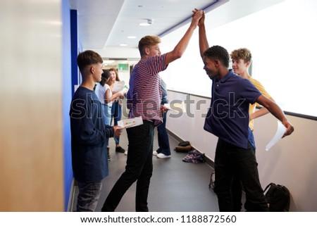 Excited Male Teenage High School Students Celebrating Exam Results In School Corridor