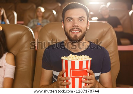 Excited male viewer keeping popcorn in hands and watching interesting film in cinema. Young bearded man wearing shirt expecting final of movie. Concept of entertainment and leisure. Stock photo ©