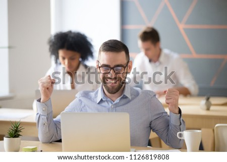 Excited male worker happy winning online lottery, smiling employee glad getting promotion letter at laptop, gaining success on market, earning money, man reading good news sitting in coworking space