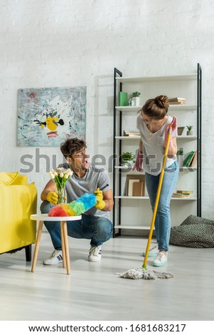 excited man and happy woman looking at each other while cleaning living room ストックフォト ©