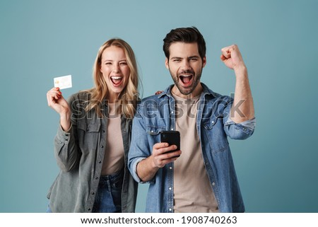 Excited man and woman making winner gesture while holding credit card and cellphone isolated over blue background