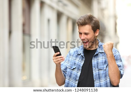 Excited man checking news on smart phone walking in the street