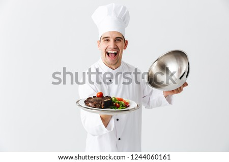 Excited man chef cook wearing uniform opening cloche cover isolated over white background, showing meat dish