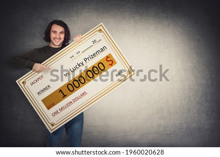 Excited man holding a lottery winner bank check. Happy guy jackpot winning one million dollars prize. Big banner announcing the main award. Wealth, luck and success concept. Becoming a millionaire Foto stock ©