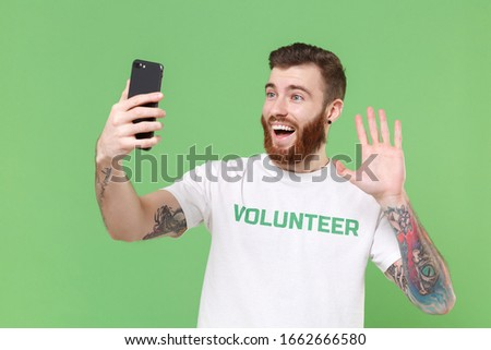 Photo of Excited man in volunteer t-shirt isolated on pastel green background. Voluntary free work assistance help charity grace teamwork concept. Doing selfie shot on mobile phone, waving greeting with hand