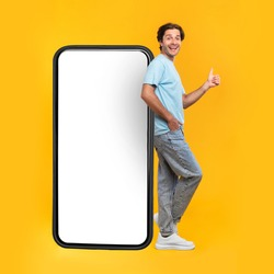 Excited Man Leaning On Big Smartphone With Blank White Screen And Gesturing Thumb Up Sign, Cheerful Guy Recommending New App Or Website, Standing On Yellow Background, Mock Up Image, Full Body Length
