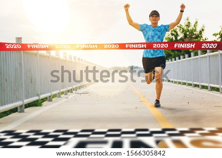 Excited man runner crossing the 2020 finish line of marathon. 2020 success concept Stock photo ©