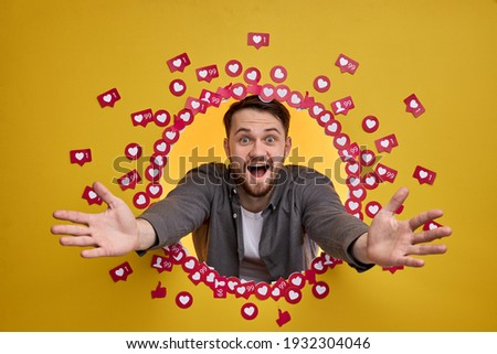 Excited Man Shine With Happiness Having Many Followers And Subscribers, Smile At Camera With Wide Opened Mouth, Among Likes, Isolated On Yellow Background Foto stock ©