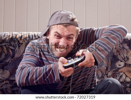 Excited man with joystick playing video games at home