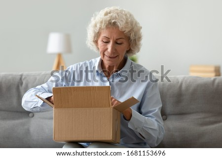 Excited mature woman sit on couch in living room open cardboard box shopping online at home, happy elderly female unpack parcel order purchase goods on Internet, good delivery concept