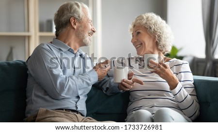 Excited middle aged hoary man chatting with joyful mature wife, relaxing on cozy sofa, drinking morning coffee. Happy old retired couple holding cups of tea, enjoying pleasant conversation at home. Photo stock ©