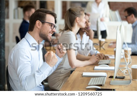 Excited millennial male employee work in shared workplace winning online lottery, happy worker gesture yes getting job promotion achieving goal, satisfied man feel euphoric reading great news online