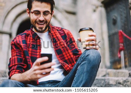 Excited millennial male getting message about victory in online lottery surprised with achievement outdoors, overjoyed young hipster guy happy about getting credit in banking via smartphone app #1105615205
