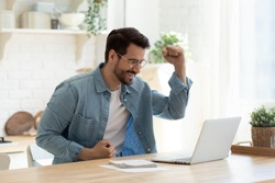 Excited millennial man in glasses sit at table in kitchen feel euphoric win online lottery on laptop, overjoyed young male in spectacles look at computer screen triumph get good news on email