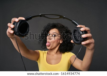 Excited mixed race african woman showing or giving you headphones showing her tongue at camera, teasing, offering to listen to music, studio portrait