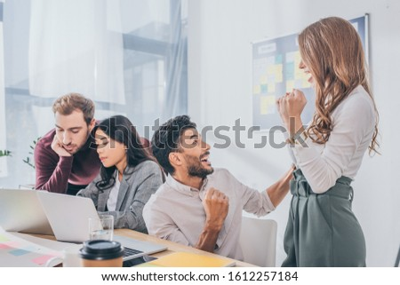 excited mixed race businessman and businessman celebrating near coworkers in office