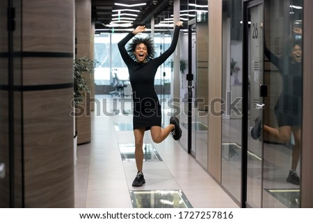 Excited mixed-race businesswoman jumps dance in office hallway raise hands scream with joy celebrates career advancement, salary growth, hired recruited African woman feels happy got dream job concept
