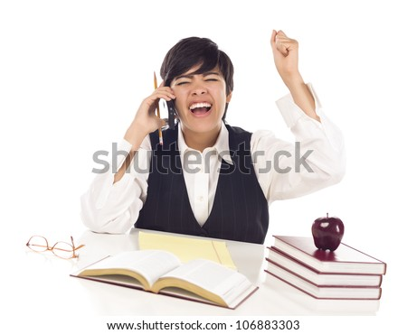 Excited Mixed Race Female Student at Desk with Books on Cell Phone Cheers Isolated on a White Background.