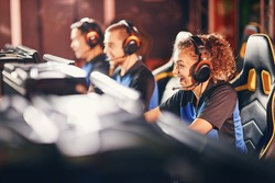 Excited mixed race girl, female gamer wearing headphones looking at PC screen and smiling while participating with team in eSport tournament