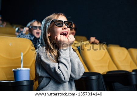 excited multicultural friends in 3d glasses watching movie in cinema together