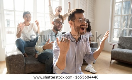 Excited multicultural friends soccer fans gathered together in sunny living room at home watching on tv sportive game feels euphoric waiting for goal, hobby, tournament viewers, sport betting concept Photo stock ©