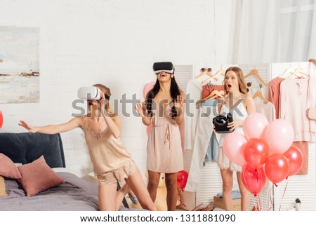 excited multiethnic girls in nightwear and vr headset having virtual reality experience during pajama party