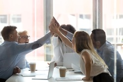Excited multiethnic work team give high five motivated for shared success at office meeting, happy diverse colleagues join hands engaged in teambuilding activity at briefing. Teamwork concept