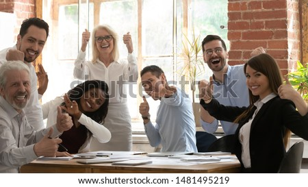 Excited multiracial businesspeople sit at office desk at meeting look at camera showing thumbs up together, overjoyed successful diverse colleagues posing for picture feel motivated at briefing