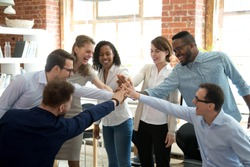 Excited multiracial colleagues give high five involved in teambuilding activity at meeting, happy diverse workers join hands celebrate success or win, show team spirit and unity. Cooperation concept