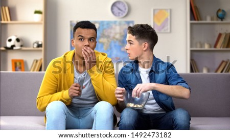 Excited multiracial male teens watching reality show, worrying about heroes