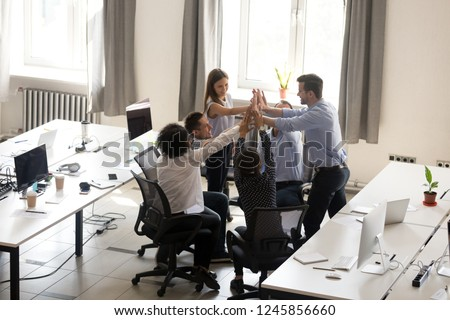 Excited multiracial office workers team giving high five together, celebrating successful teamwork results, involved in team building activity, good corporate relations, motivated by success