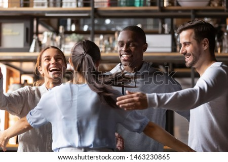 Excited multiracial young people hanging out together in cafe meeting new girlfriend giving hug, happy diverse friends feel overjoyed welcoming colleague relaxing having fun in bar or restaurant
