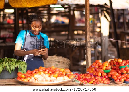 excited nigerian market woman feeling excited while using her phone Foto stock ©